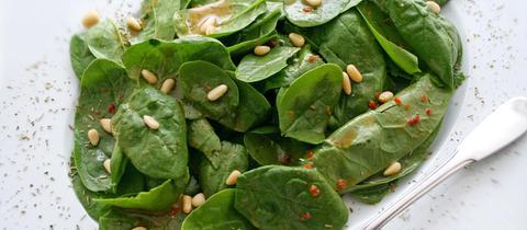 Spinatsalat mit Pinienkernen.
