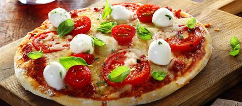 Eine Pizza mit Tomaten, Mozzarella und frischem Basilikum.