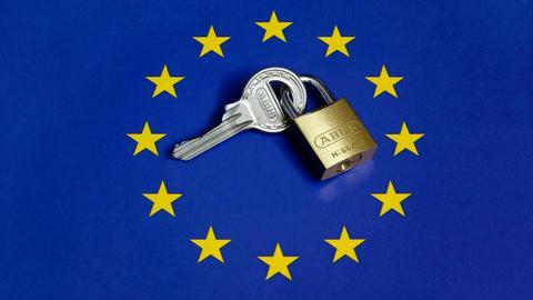 Ein Sicherheitsschloss mit einem Schlüssel liegt auf einer EU-Fahne.