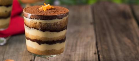 Ein Dessertglas mit geschichtetem Tiramisu, garniert mit Orangenzesten.
