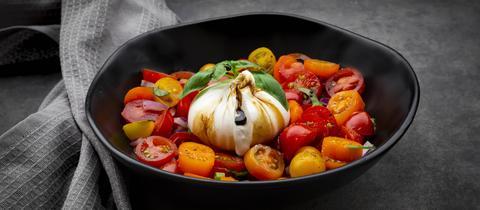 Eine kleine Schüssel Tomatensalat mit Burrata.
