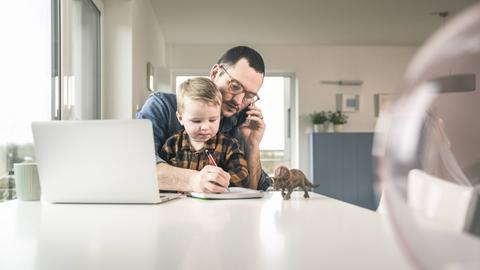Mann betreut sein Kind während er im Homeoffice arbeitet