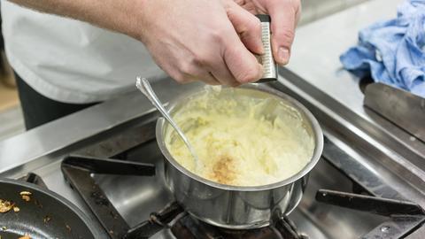 Ein Koch reibt eine Muskatnuss in einen Topf mit Kartoffelpüree.