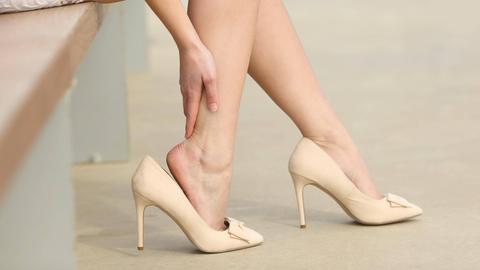 Eine Frau trägt High Heels und fasst sich ans schmerzende Bein.