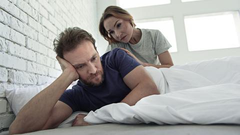 Ein Mann liegt in einem Bett, stützt sich auf seine Hand ab und starrt ins Leere. Eine Frau sitzt hinter ihm und legt besorgt eine Hand auf seine Schulter.