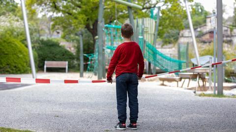 Junge steht vor einem abgesperrten Spielplatz