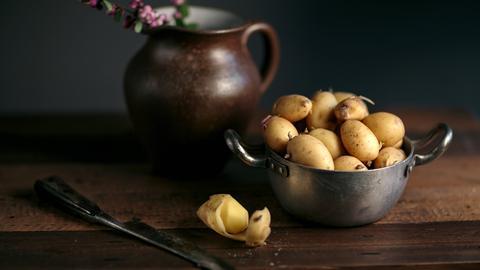 Pellkartoffeln in einem silbernen Topf, eine Kartoffel liegt neben einem Messer geschält neben dem Topf.