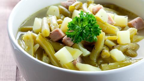 Eine weiße Schale mit Bohneneintpf, Speck und Kartoffeln.