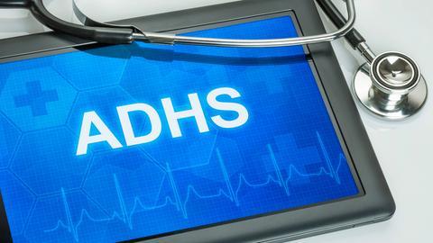 Die Buchstaben ADHS sind in weißer Schrift auf blauem Grund auf einem Tablet zu lesen. Daneben liegt ein Stethoskop.
