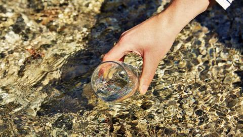 Frauenhand hält ein Glas Wasser über einer Wasseroberfläche (mutmaßlich See oder Bach).