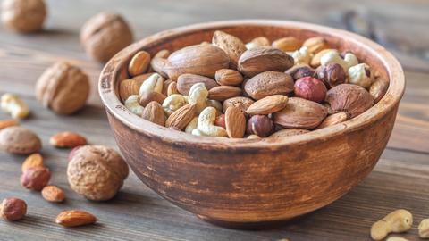 Eine hölzerne Schüssel voll Nüssen: Mandeln, Haselnüsse, Cashews.