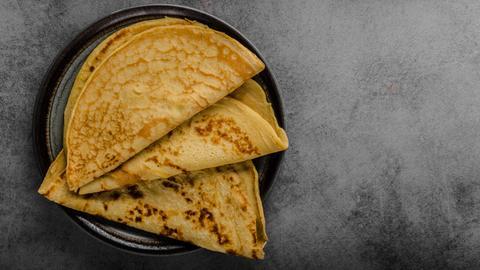 Drei dünne Pfannkuchen (Crepes-ähnlich) liegen zusammengefaltet auf einem dunklen Teller.