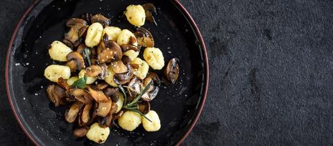Gnocchis und Pilze in einer Pfanne.
