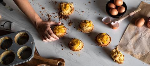 Blick auf mehrere Pfirsich-Cupcakes von oben auf eine Küchenzeile.