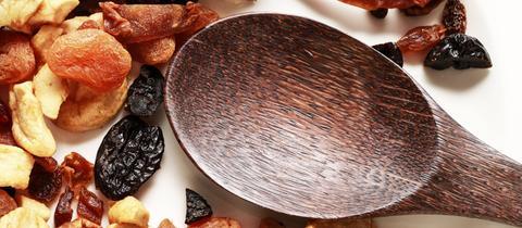 Ein Läffel aus Holz neben getrockneten Früchten wie Aprikosen, Rosinen und Cranberries auf hellem Untergrund.