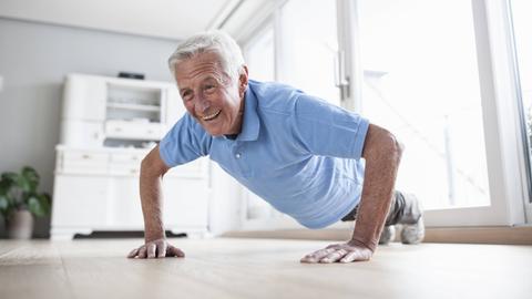 Ein älterer Mann macht zu Hause Liegestütze und freut sich dabei.