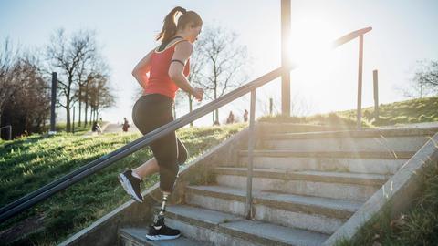 Eine sportliche junge Frau mit einer Beinprothese joggt eine Treppe hoch.