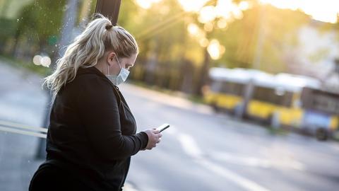 Frau steht mit Mundschutz an der Bushaltestelle