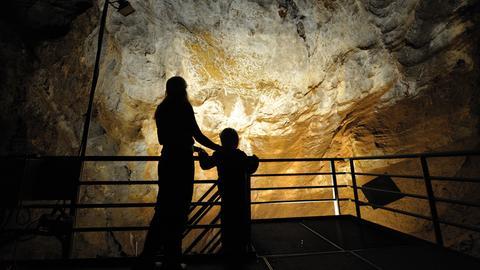 Eine Besucherin und ihr Kind betrachten die Südhalle der Kristallhöhle in Kubach