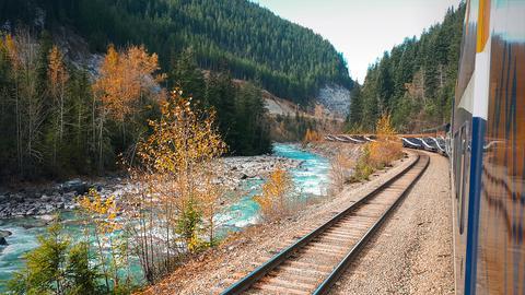 Ein Zug fährt durch eine Berglandschaft in Kanada