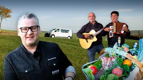 Klaus Breinig, ein Korb voller Lebensmittel und zwei Protagonisten mit Gitarre und Akkordeon auf einem Feld mit einem Fahrzeug im Hintergrund.
