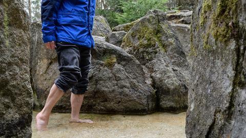 Mann steht barfuß in kaltem Wasser.
