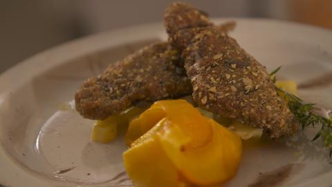 Alis Hauptspeise: Rehschnitzel in Kürbiskernpanade mit süß-saurem Hokkaido auf weißem Teller angerichtet.