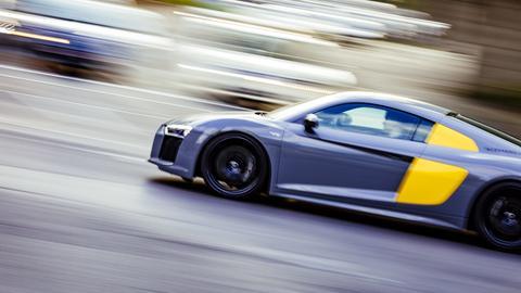 Ein Sportwagen fährt zügig über die Straße.