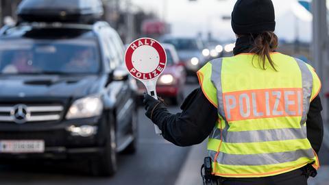 Eine Polizistin hält ein Auto an.