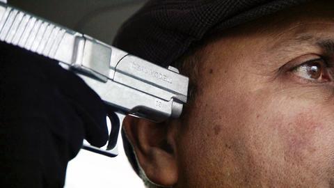 Ein Mann wird mit einer Pistole am Kopf bedroht.