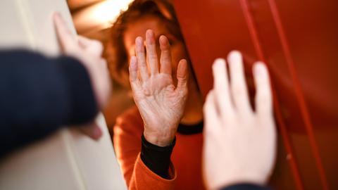 Ein Einbrecher überfällt eine Seniorin an der Haustür. Sie hält sich abwehrend die Hände vors Gesicht.