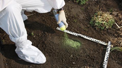 Kriminaltechniker sichert einen Schuhabdruck an einem Tatort. Sichtbarmachung mit grüner Sprühfarbe und Abnehmen eines Gipsabdrucks.