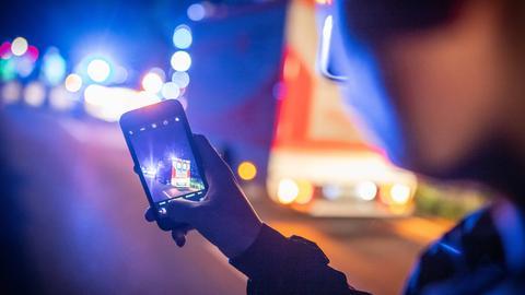 Symbolbild von einem Gaffer mit seinem Smartphone bei einem Feuerwehr/Rettungsdiensteinsatz.