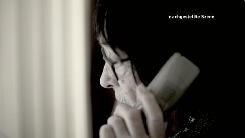 Eine ältere Frau hält sich einen Telefonhörer ans Ohr. Schwarzweißbild. Nachgestellte Szene.