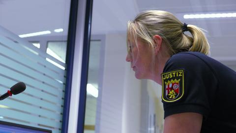 Eine Polizistin schaut auf Computer-Bildschirme.