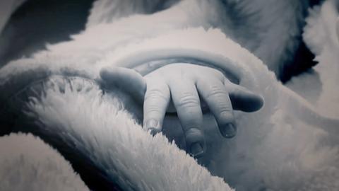 Eine babyhand schaut aus einer Decke