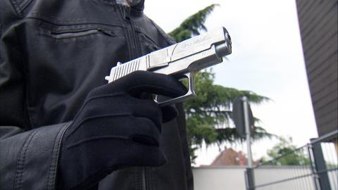 Mann bedroht jemanden mit einer Waffe.