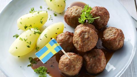 Köttbular mit Salzkartoffen und Preiselbeerdip auf einem Teller.