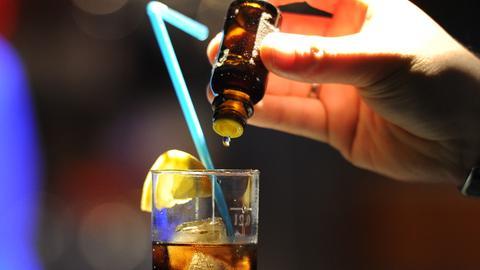 Aus einem Fläschchen werden Tropfen in ein Getränk geträufelt.