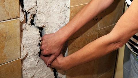 Eine Frau hält ihre Hand in einen Riss in der Wohnungswand.