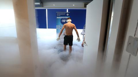Ein Mann verlässt, mit Mundschutz, Stirnband und Handschuhen geschützt, in einem Fitnessstudio die Kältesauna aus deren Tür die kalte Luft abfließt und Nebel bildet