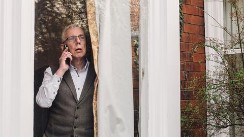 Älterer Mann telefoniert am Fenster.