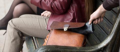 Ein Taschendieb greift nach einem Portemonnaie in einer Tasche.