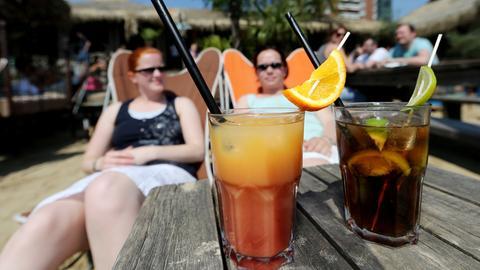 Zwei Frauen trinken Cocktails an einer Strandbar