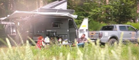 Protagonisten sitzen mit Camping-Fahrzeug und Zelt im Feld.