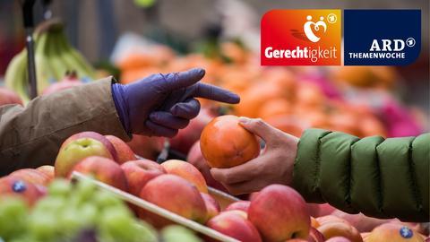 Ein Kunde hält an einem Markstand ein Stück Obst in der Hand.