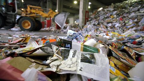 Gesammeltes Altpapier auf dem Firmengelände der Rauch Recycling GmbH. Im Hintergrund ist ein Bagger zu sehen.