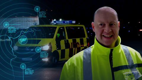 Protagonist in neongelber Jacke steht vor einem Fahrzeug.