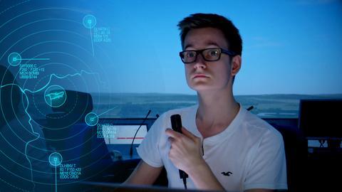 Junger Protagonist sitzt im Tower und hält ein Mikrofon in der Hand.