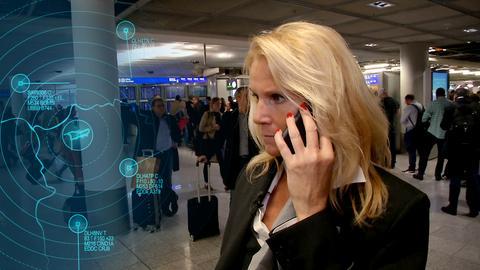 Terminal Duty Managerin Catharina Jud telefoniert. Im Hintergrund stehen viele Menschen in einer Warteschlange.